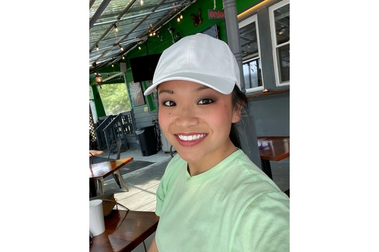 A woman wearing a white hat and a green shirt is smiling in front of a restaurant.