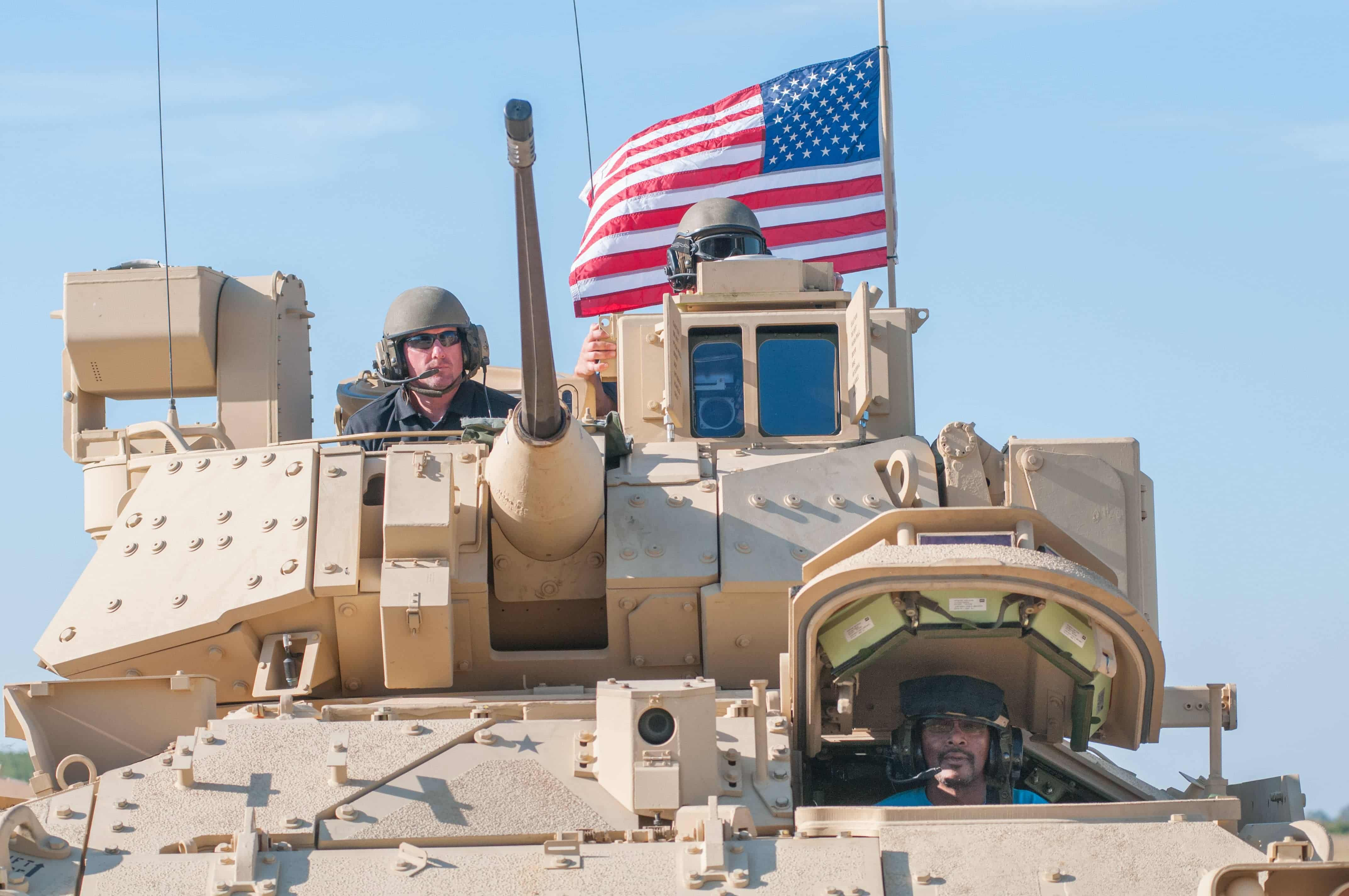 A civilian contractor and Soldier ride in a Bradley tank with an American flag in the background.