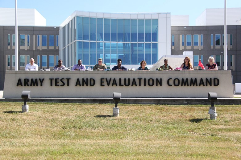 People stand behind a concrete sign that says Army Test and Evaluation Command outside of the headquarters building