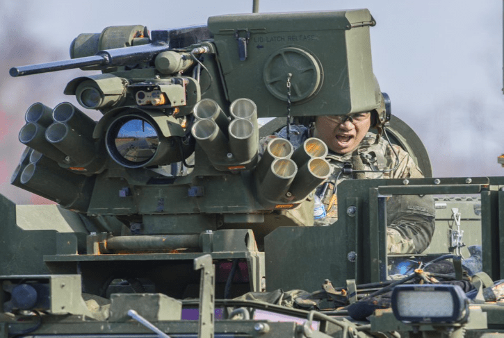 A soldier is sitting at a gun turret.
