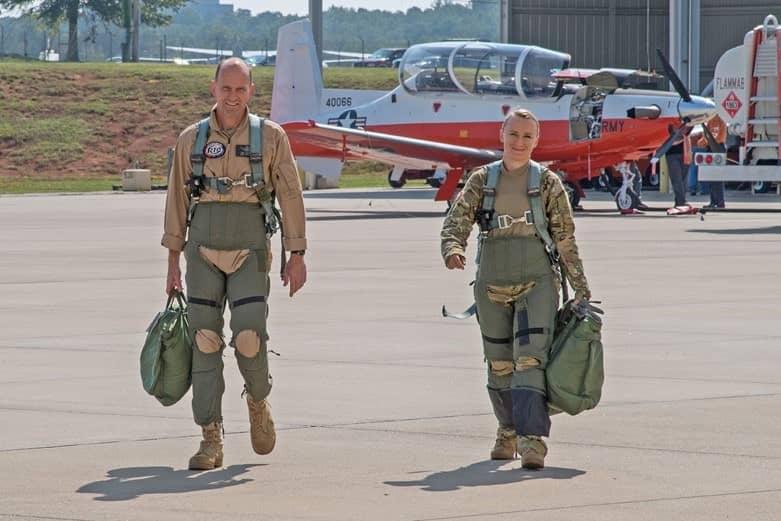Two Airmen walk across a landing strip at an airport.