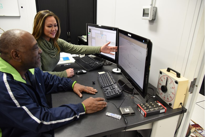 A man and a woman review a statistical graph on a computer screen.