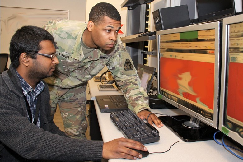 A civilian and a Soldier work together at a computer terminal.