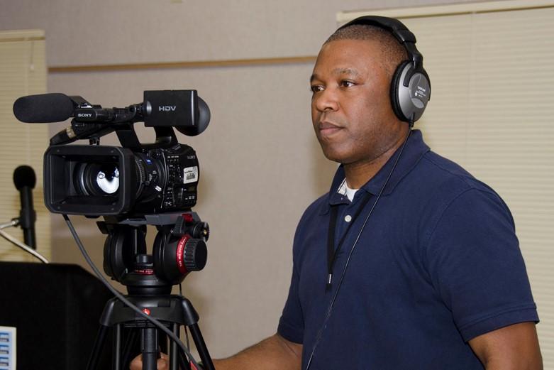 A civilian uses a video camera on a tripod.