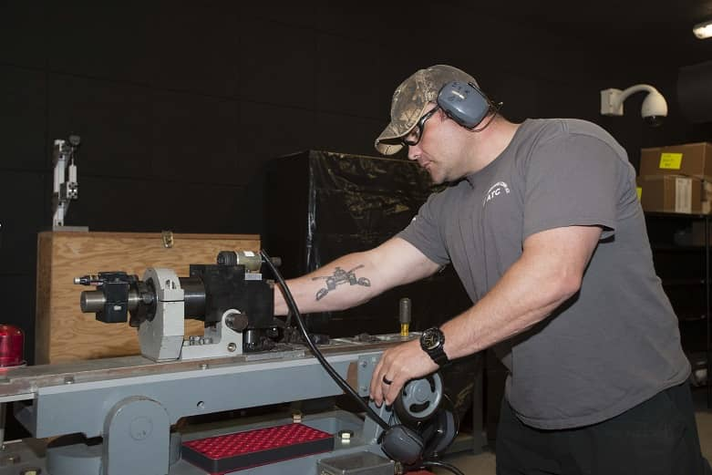 A man works on machinery while wearing ear protection.
