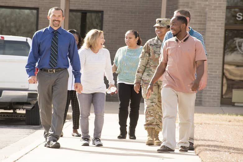 A group of civilians and one Soldier walk through a parking lot while sharing a laugh.