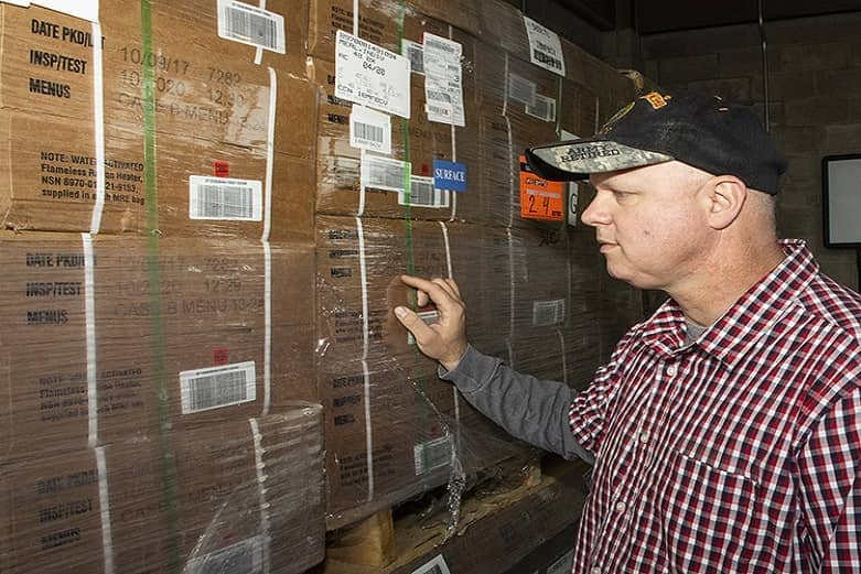 A civilian inspects the labels on multiple cardboard boxes.