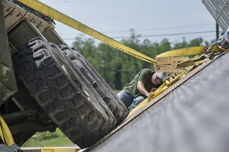 A civilian worker lays on the ground inspecting the underneath of a military tactical vehicle.
