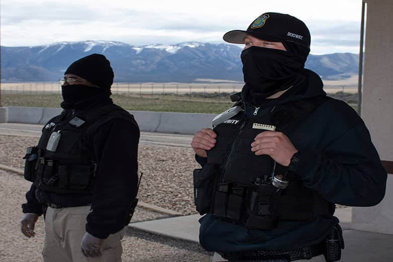 Two security guards in black uniforms stand watch in an open area.