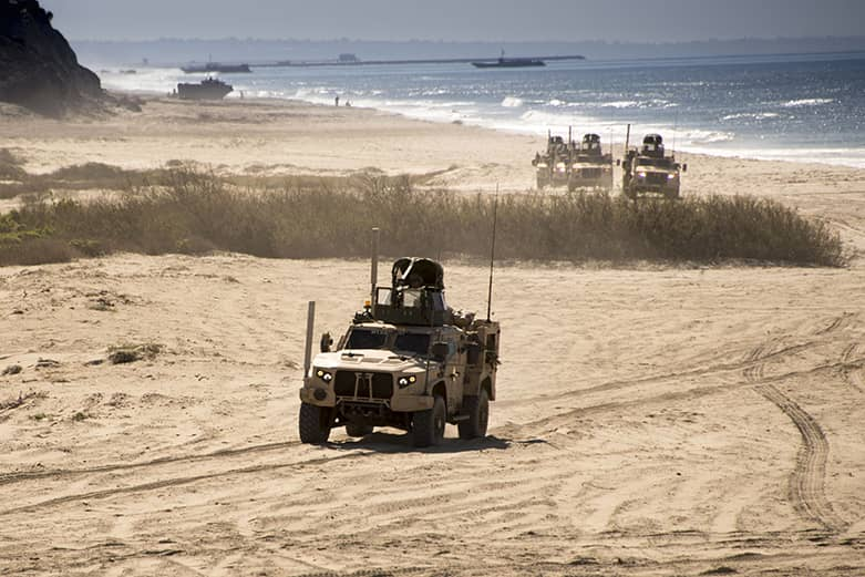 A tactical military vehicle is part of a convoy going through a sandy environment.