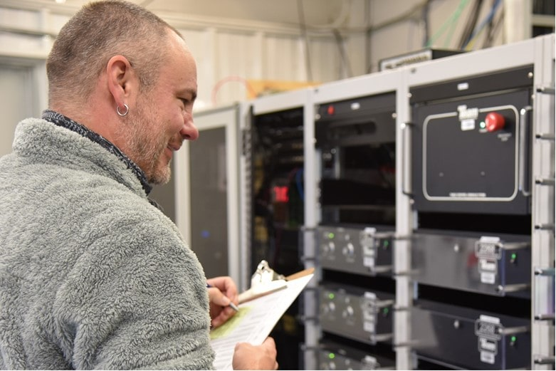An engineer inspects computer equipment.