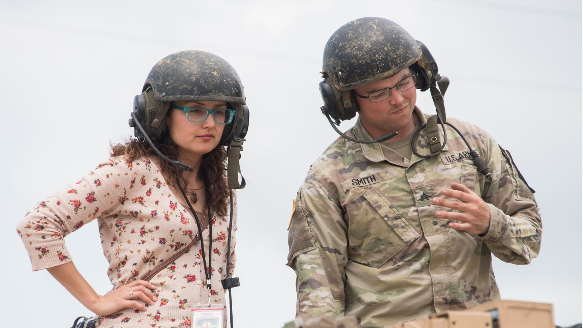 A female civilian with an Army helmet and a Soldier have a discussion on top of a military vehicle.