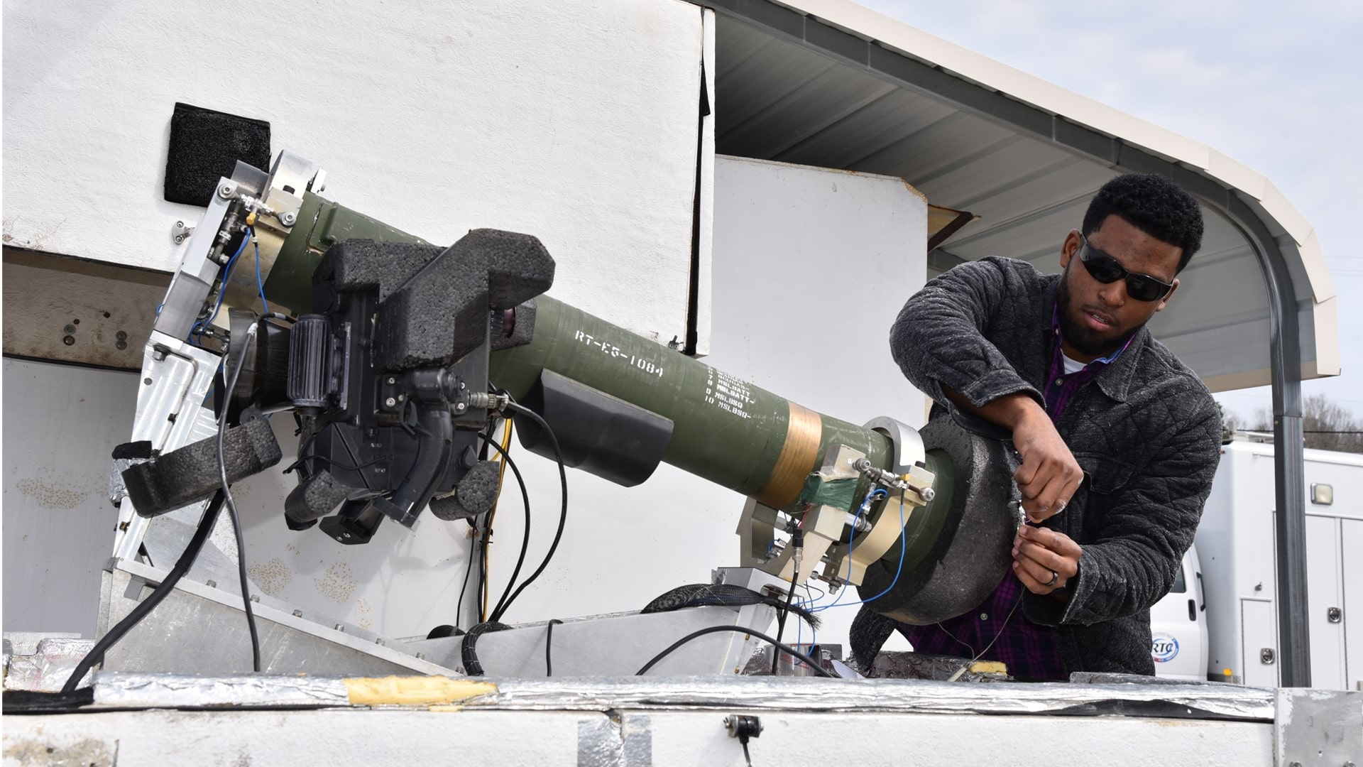 A civilian is fixing a piece of a TOW anti-tank missile launcher.
