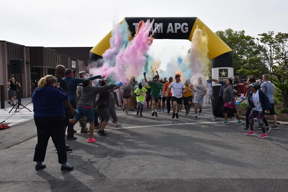 A group of runners crosses the finish line of a color run