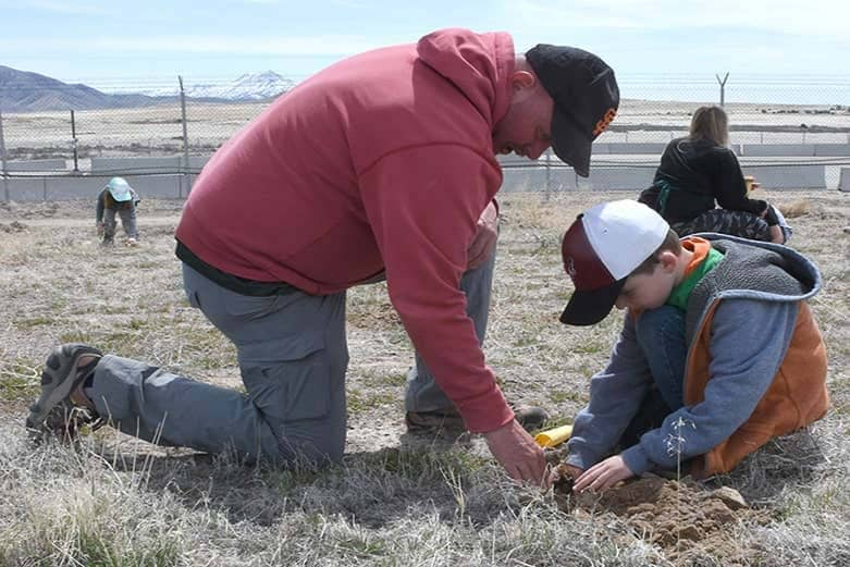 A father and son kneeling in a grassy open field are playing with something on the ground.