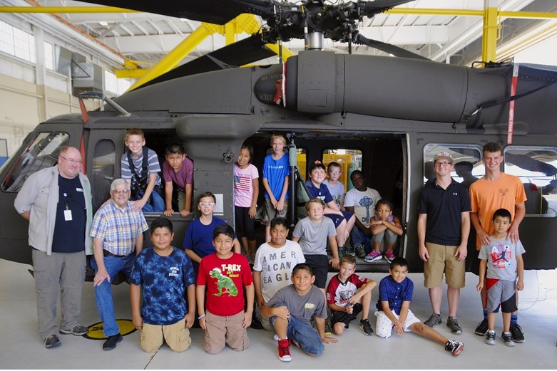 A teacher and his students pose in front of a helicopter.